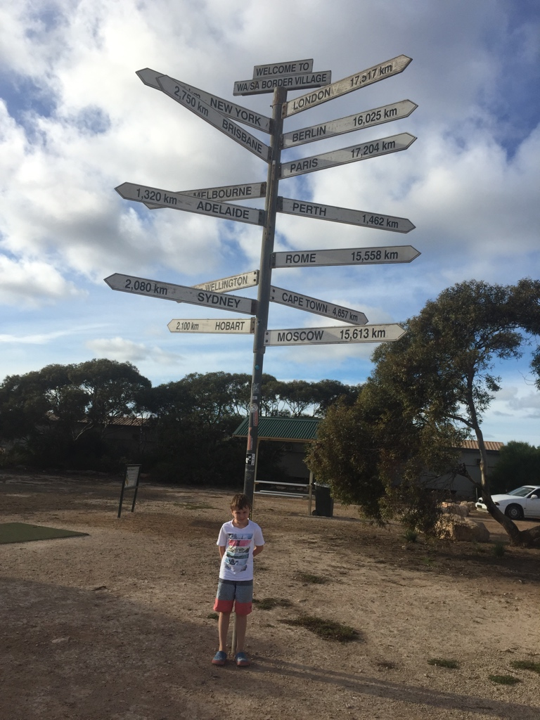 Aaron with a sign that tells us we are a long way from anywhere!
