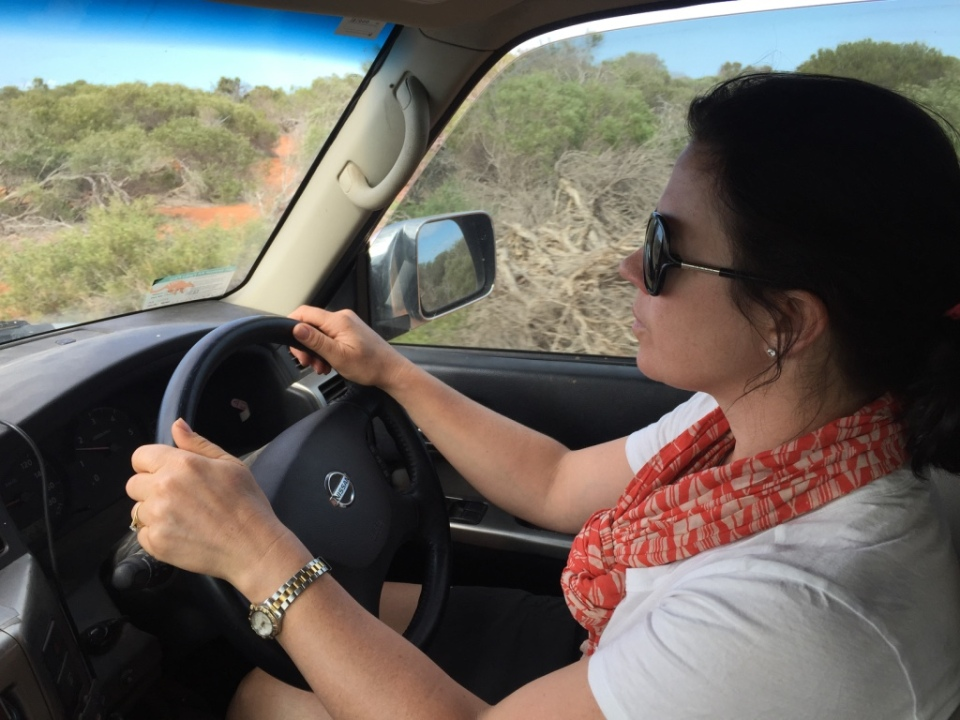Michaela behind the wheel on the sandy tracks.