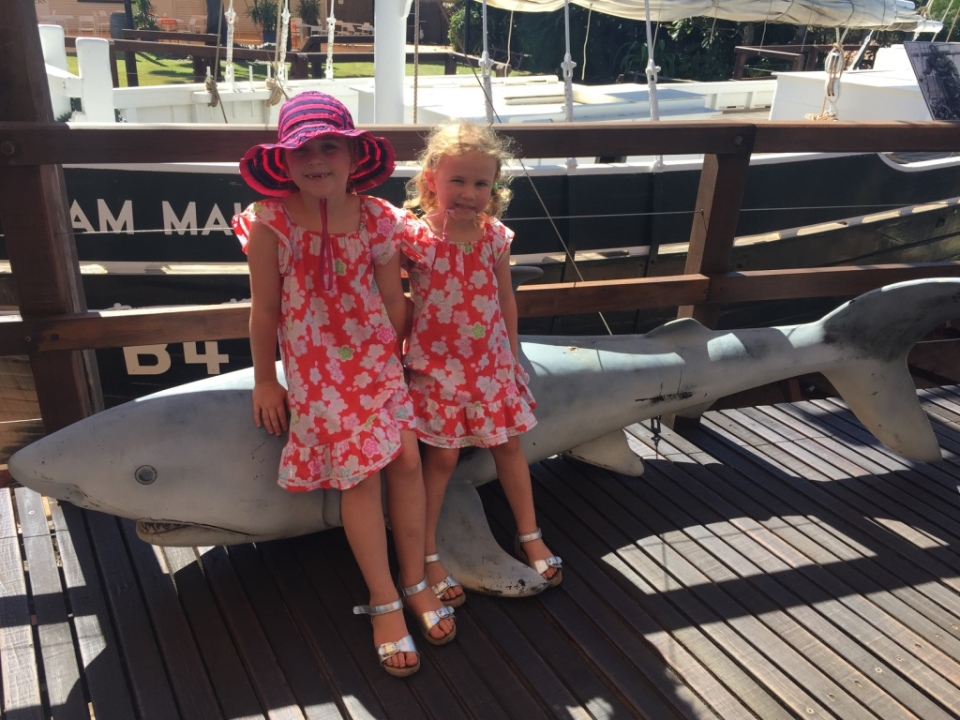 Girls next to a shark and pearl lugger boat